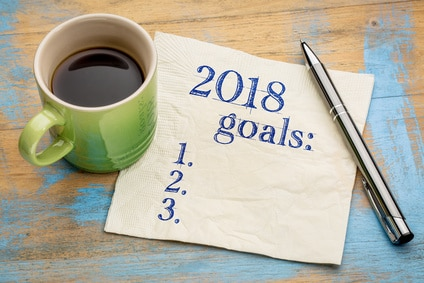 cup of coffee sitting next to 2018 goals