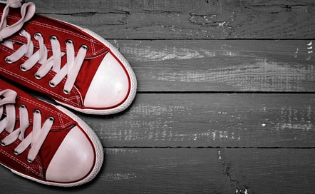 Rd converse sneakers on a wooden floor