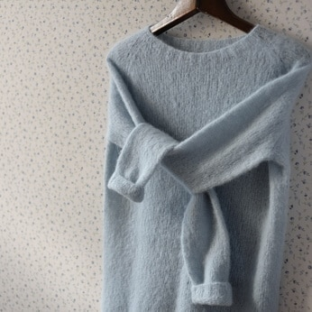 blue cashmere sweater on a wooden hanger with the arms crossed